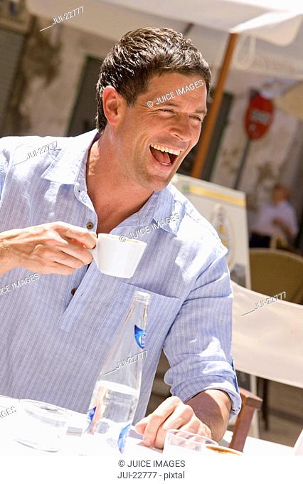 Man laughing and drinking coffee at sunny, outdoor cafe