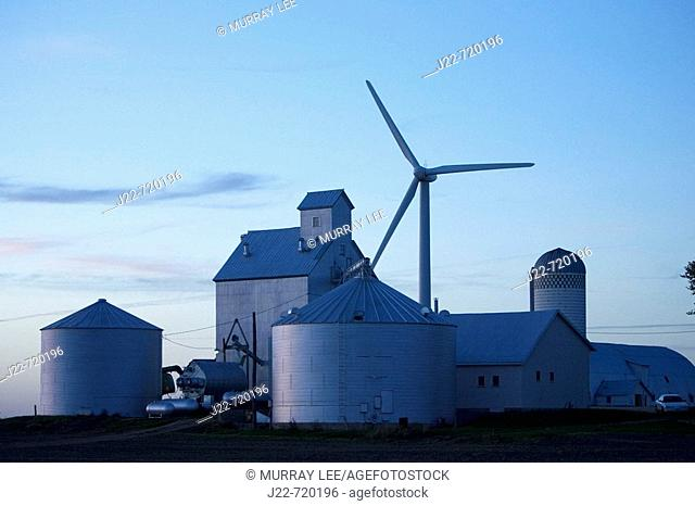 Modern grain handling facility with wind generator towering over it on Iowa farmstead near Williams, Iowa, USA  Photo shows grain elevator tall structure