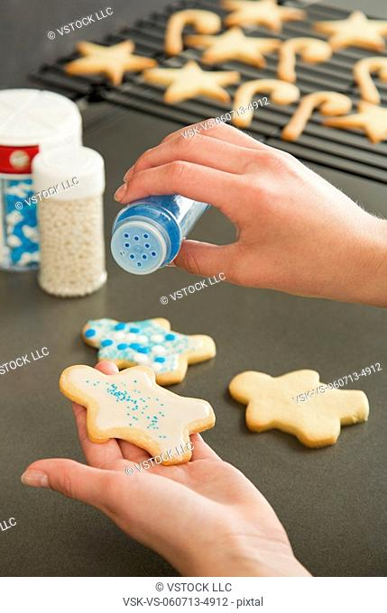 Girl (12-13) decorating cookies with sprinkles