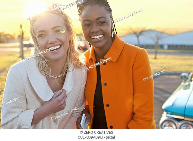 Women smiling for camera in front of vintage car