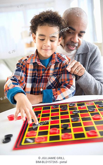 Mixed race grandfather and grandson playing checkers