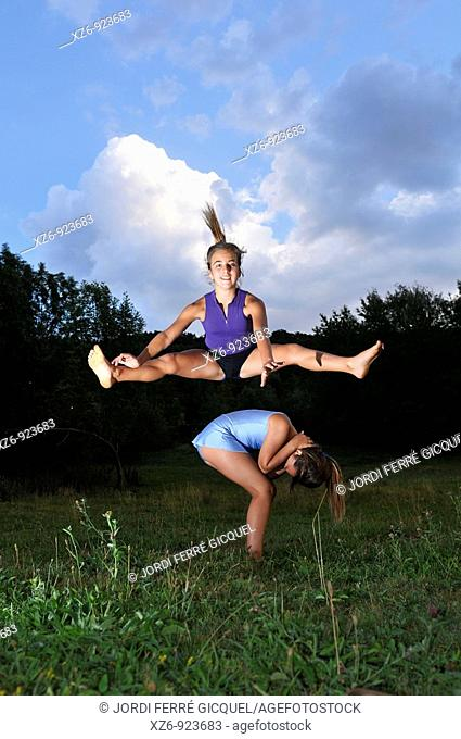 two young gymnasts jumping in a meadow at dusk