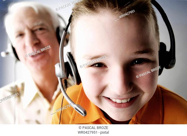 Portrait of a grandfather and his grandson wearing headsets