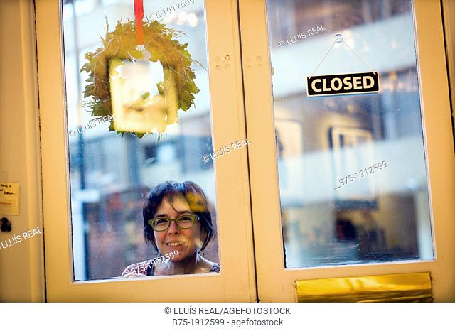 young woman looking inside through a closed door in Soho, London, England, UK