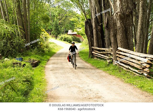 A woman, 66, bicycles on a country road on Saturna Island, Gulf Islands, British Columbia, Canada