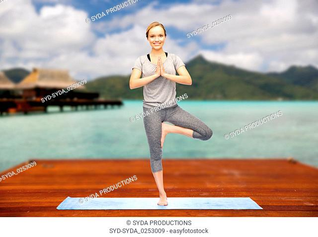 woman making yoga in tree pose outdoors