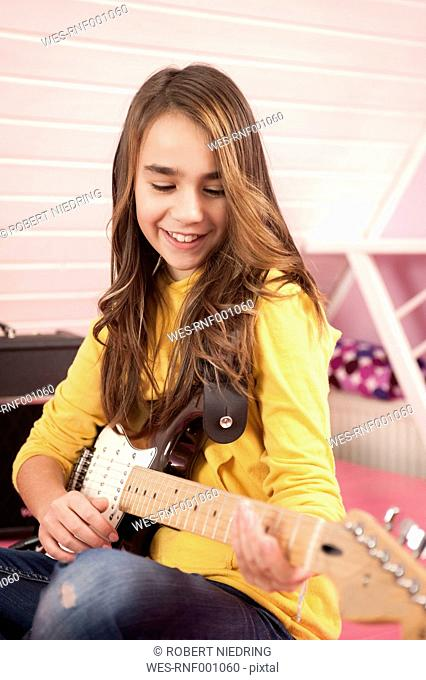 Girl playing guitar, smiling