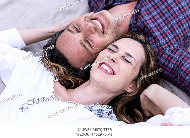 Happy affectionate couple lying on a blanket