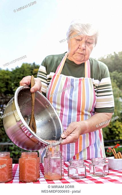 Senior woman pouring homemade applesauce in jam jars