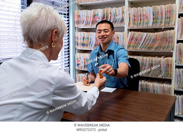 Young Asian male doctor and senior patient interacting with each other at clinic