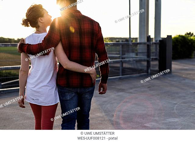 Young couple arm in arm at sunset