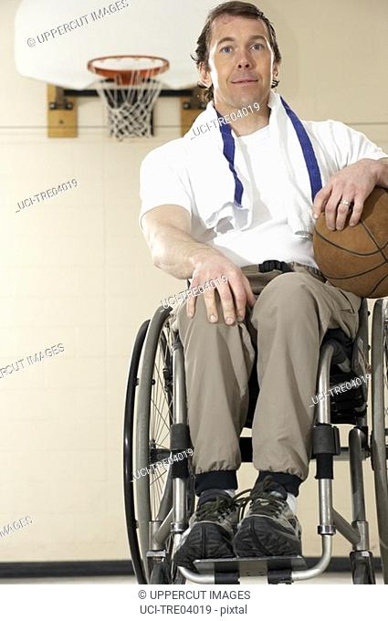 Wheelchair-bound man holding basketball
