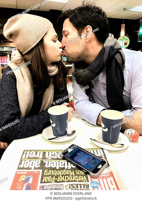 couple kissing while taking a break at table at gas station's café with newspaper Bild and phone laying on table and paper cups of coffee in Munich, Germany