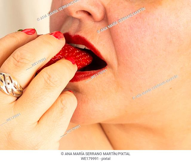 An adult woman with red nails and lips eating a strawberry