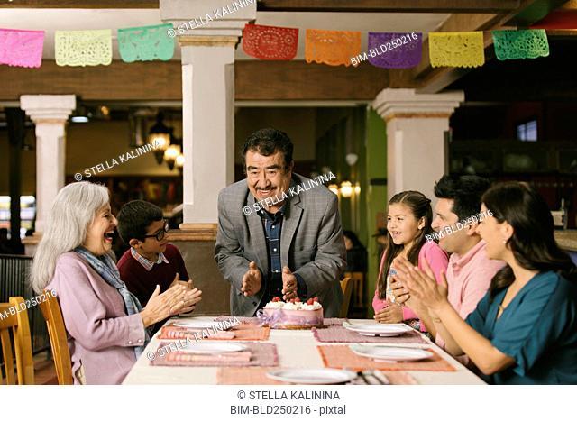 Family celebrating birthday of older man in restaurant