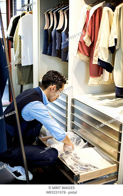 Japanese salesman with moustache wearing glasses kneeling in front of open drawer in clothing store