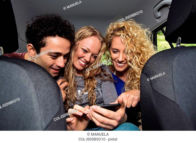 Friends in back seat of car looking at smartphone