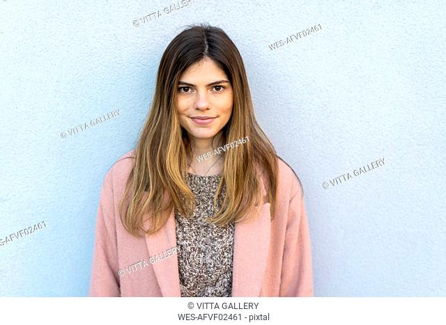 Portrait of a confident young woman at a wall