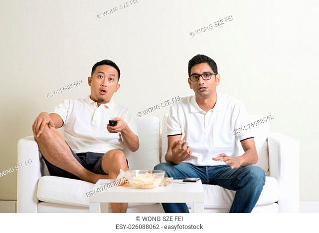 Group of men sitting on sofa watching sport together at home