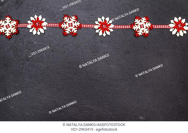 snowflakes of felt on a black stone background, empty space at the bottom