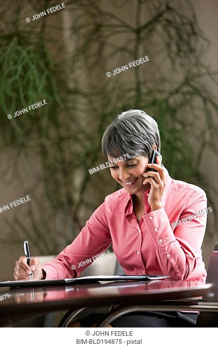 Mixed race businesswoman writing and using cell phone