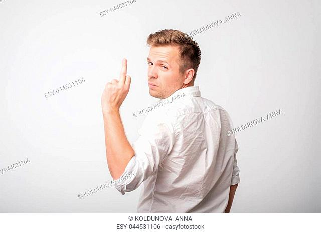 Portrait of a caucasian man in whiteshirt showing fuck you sign turning back. He does not care about problems. Concept of impolite and rude behavior