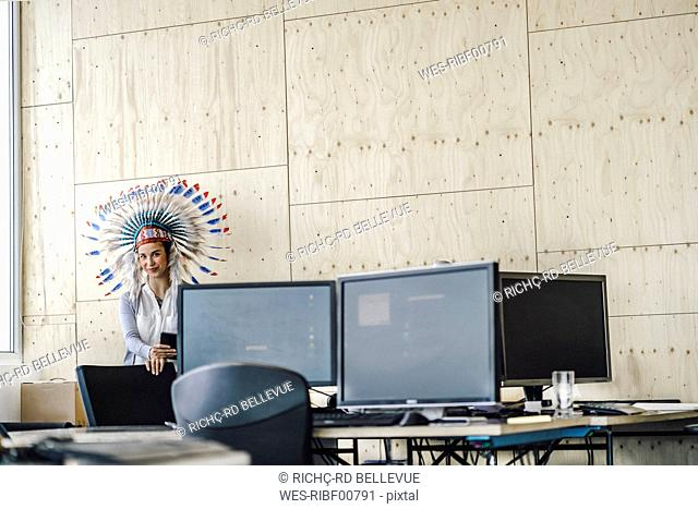 Young woman wearing Indian headdress, standing in office