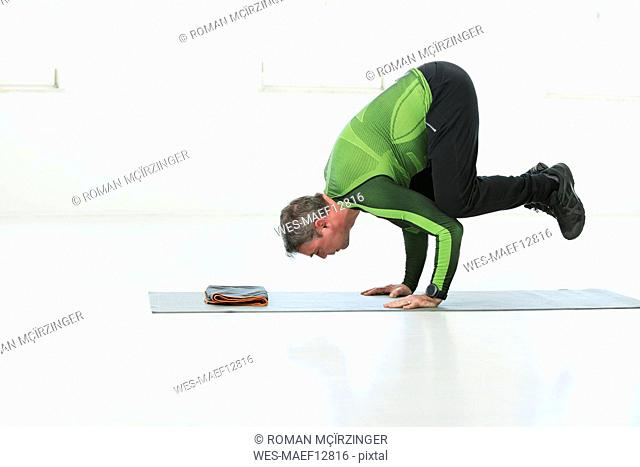 Man doing his fitness regime, practising yoga poses