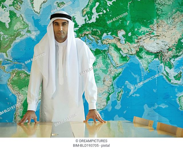 Serious Middle Eastern man in traditional clothing in conference room
