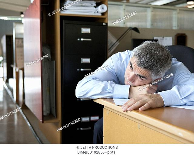 Caucasian businessman laying on desk
