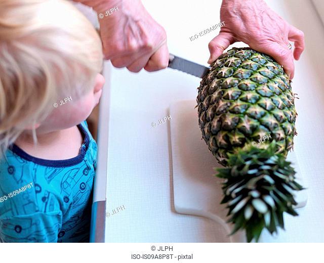 Boy watching woman slicing pineapple