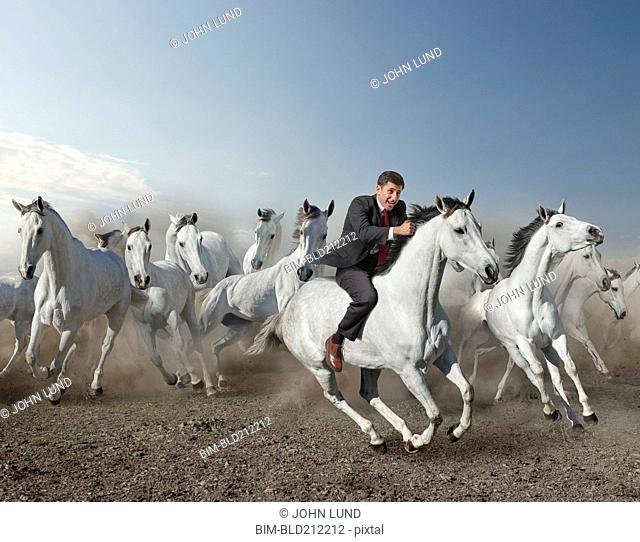 Caucasian businessman riding wild horse in desert