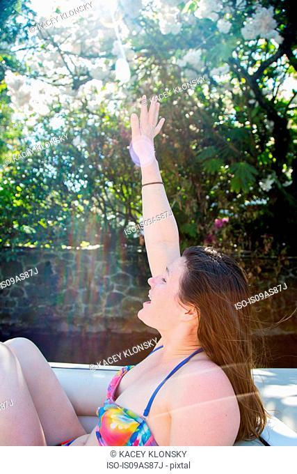 Young woman wearing bikini waving from motor boat, Lake Oswego, Oregon, USA