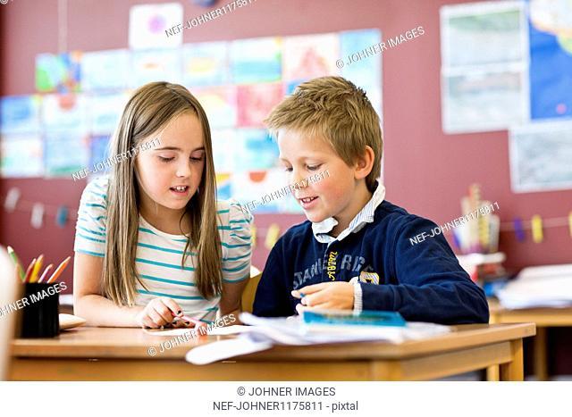 Schoolboy and schoolgirl in classroom