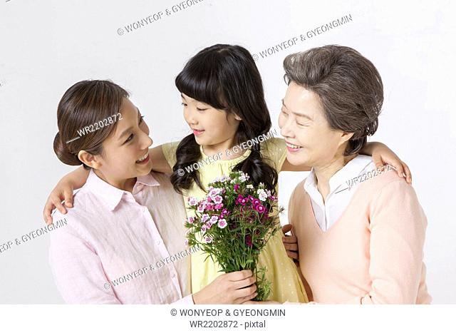 Young girl putting her arms around the young adult woman and senior woman holding flowers and all looking at each other