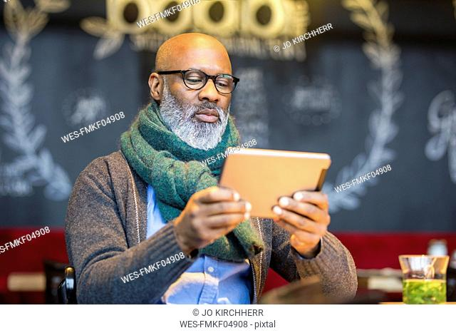 Portrait of man using tablet in a coffee shop