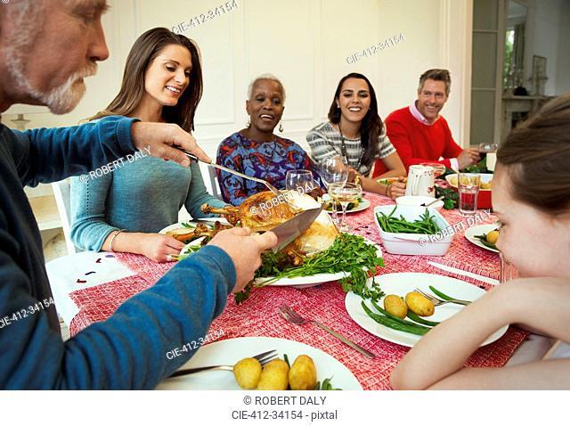Family enjoying Christmas turkey dinner at table