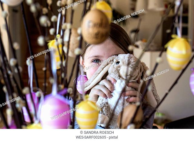 Girl hiding behind Easter bunny and twigs of pussy willows decorated with Easter eggs