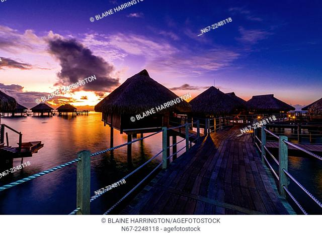 Overwater bungalows at sunset, Hilton Moorea Lagoon Resort, island of Moorea, French Polynesia