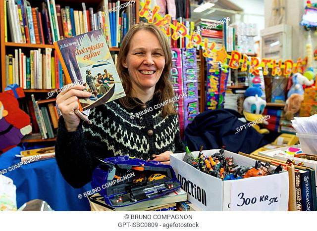 BOOKSELLER SHOWING A COPY OF THE BOOK 'JOURNEY TO THE CENTER OF THE EARTH' BY JULES VERNE, TRANSLATED INTO ICELANDIC, KOLAPORTID FLEA MARKET, REYKJAVIK