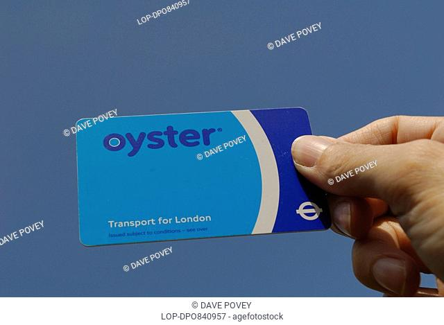 England, London, -, Oyster card held up against the sky. The Oyster card has been adopted throughout London to permit easy payment on public transport