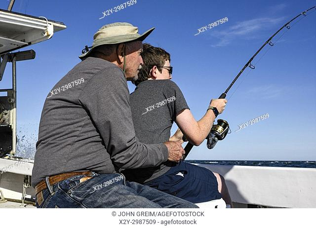Grandfather encourages grandson on bringing in a large fish, Chatham, Cape Cod, Massachusetts, USA