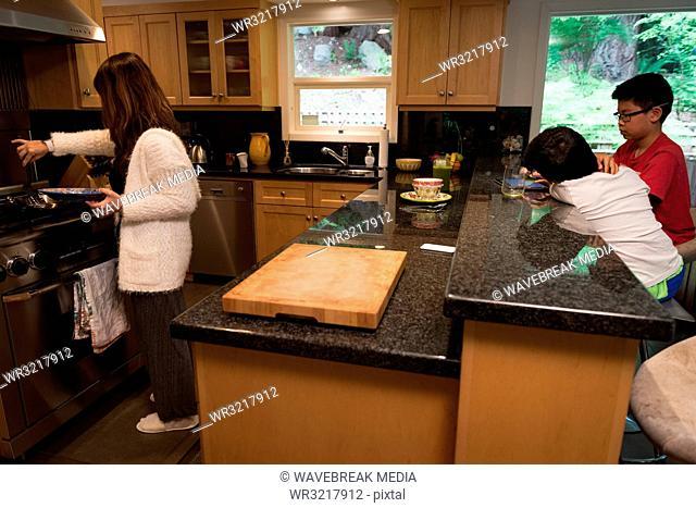 Kids using digital tablet while mother preparing food in kitchen