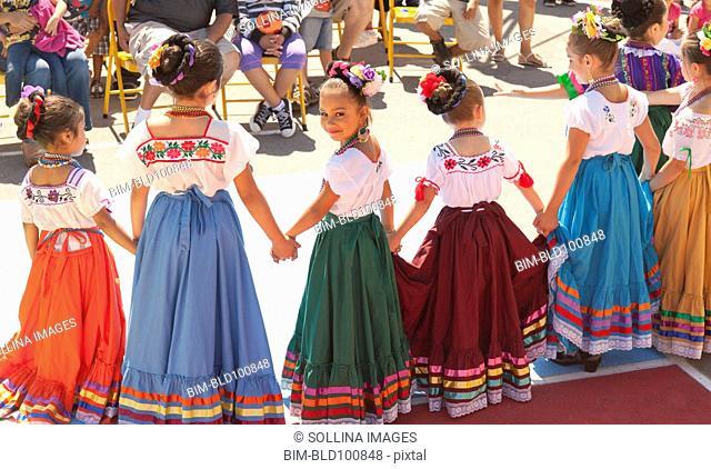 Hispanic girls dancing in costumes