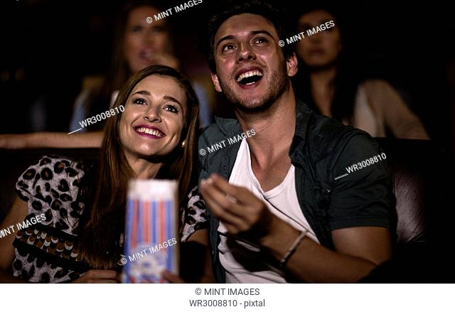 Two young people sitting in a cinema watching a film and eating popcorn