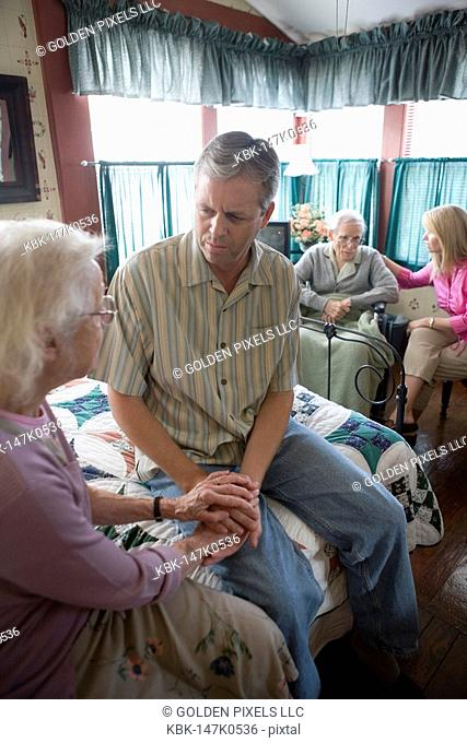 Adult children visiting and comforting senior parents in bedroom