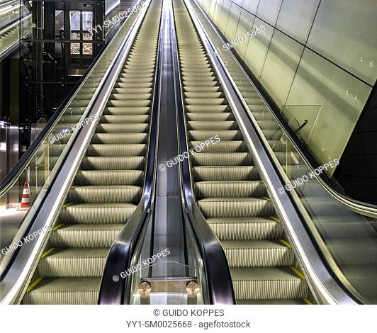 Amsterdam, Netherlands. Long and Huge escalators leading up from a deeply build Rokin Subway Station