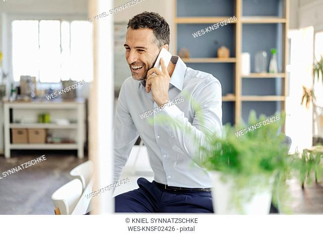 Happy businessman in office on cell phone