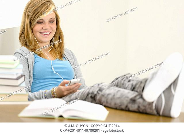 Relaxed student teenager with legs on table stack of books