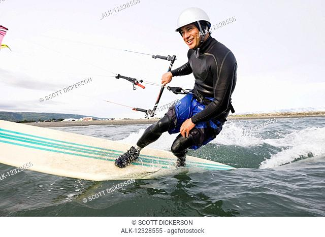 Man kitesurfing in Kachemak Bay, South-central Alaska; Homer, Alaska, United States of America